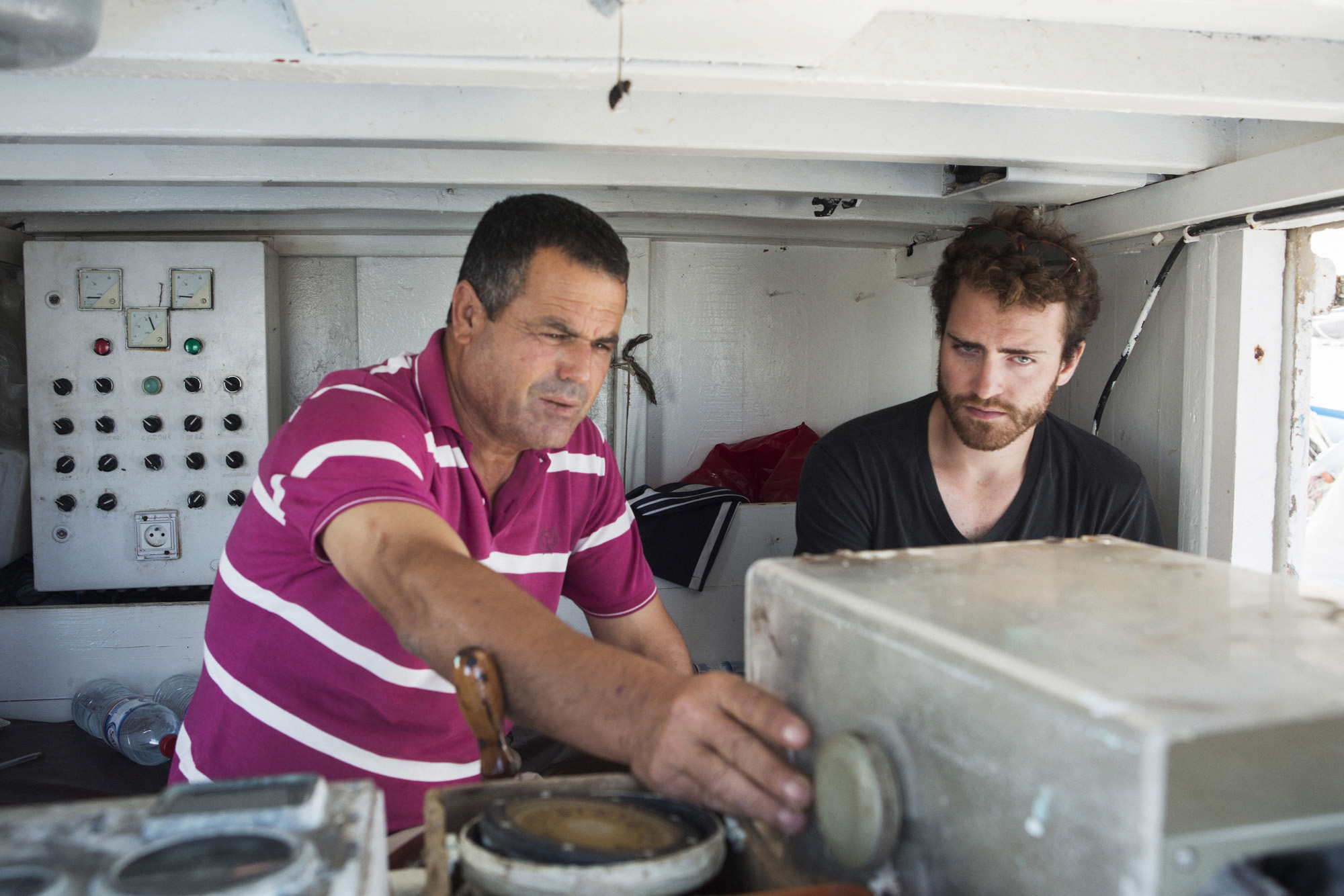 KRATEN, KERKENNAH ISLANDS, TUNISIA - 22 OCTOBER 2015: (L-R) Fisherman Hedi Khecherem, 50, shows Eric Reidy the migrant routes from Libya and Tunisia towards to Italy on his GPS on his boat in Kraten, Kerkennah Islands, Tunisia, on October 22nd 2015.